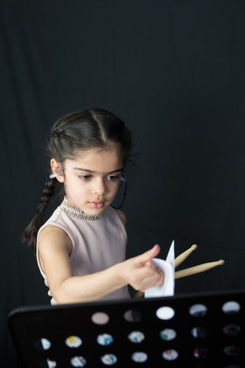 Girl Playing Drum While Standing Against Curtain