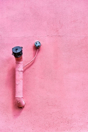 Close-up of pipes on pink painted wall