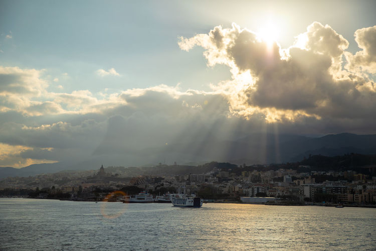 Messina Italy Sicily Ferry Sea Sky Cloud - Sky Water Architecture Building Exterior Built Structure Nature Waterfront Sunlight No People City Nautical Vessel Building Transportation Sunbeam Beauty In Nature Scenics - Nature Mountain Outdoors Sun Cityscape
