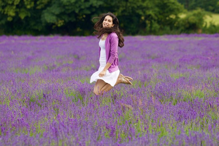 Portrait of smiling young woman jumping on lavender field