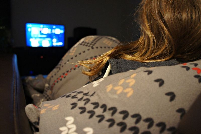 Rear View Of Woman Watching Tv At Home