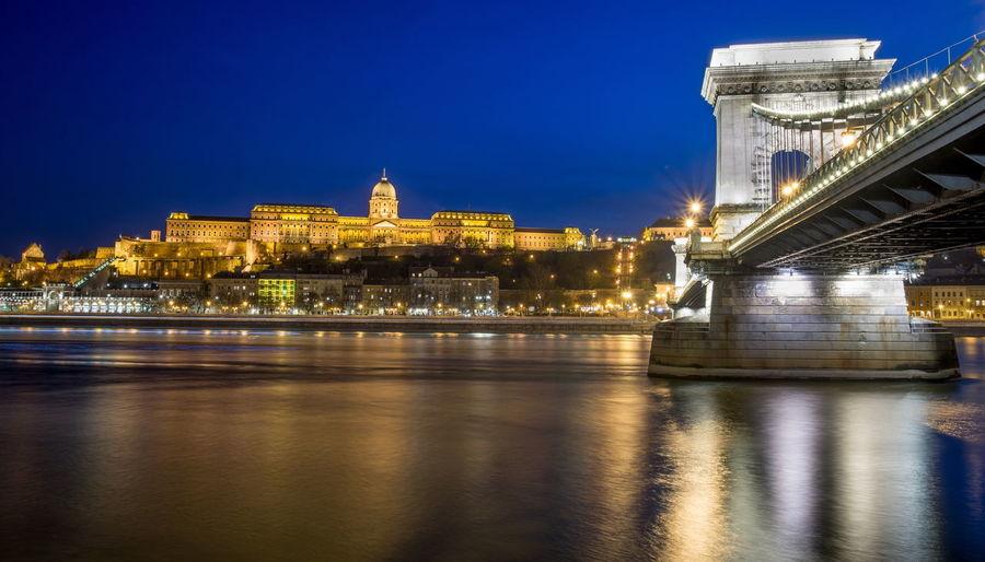Szechenyi chain bridge over danube river against sky in city at night