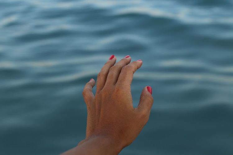 Cropped image of woman hand by sea