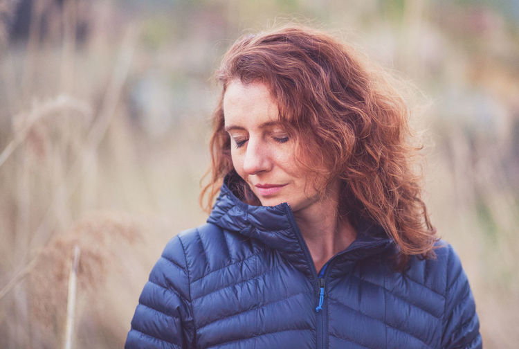 Smiling woman with closed eyes standing outdoors