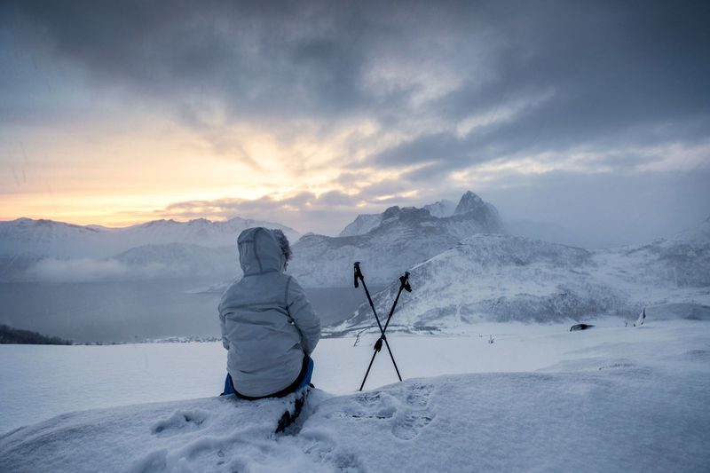 Rear view of man sitting on snow covered land against mountains and sky during winter