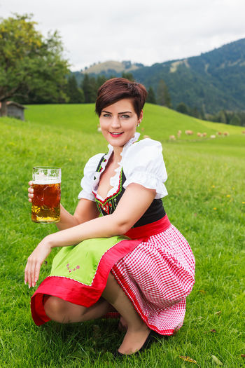 Portrait Of Mid Adult Woman Having Beer While Crouching On Grassy Field