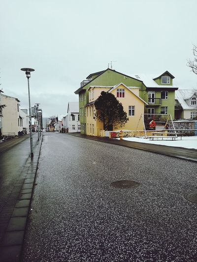Street by buildings against clear sky