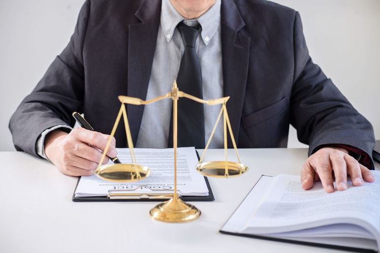 Midsection of judge sitting at table against white background