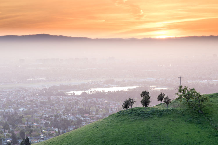 Scenic View Of Fog Covered City From Green Mountain During Sunrise