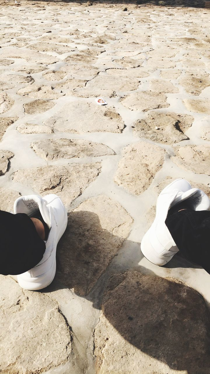real people, two people, sand, high angle view, day, sunlight, beach, leisure activity, low section, human leg, shadow, men, outdoors, lifestyles, standing, women, nature