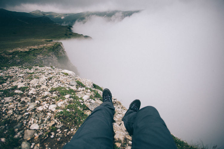 Low section of man lying on mountain peak against fog