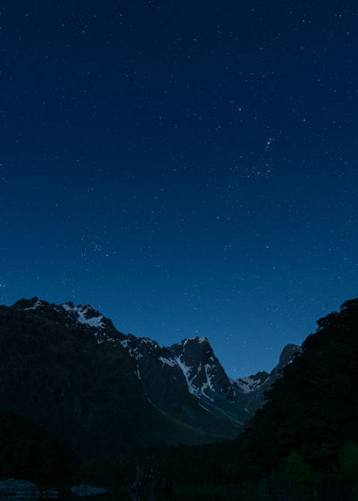 Low angle view of snowcapped mountains against starry sky at night