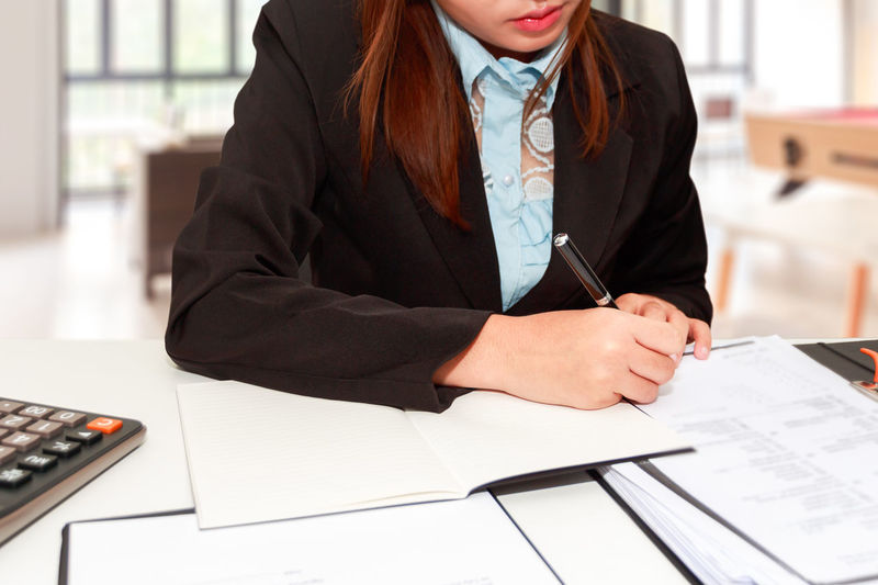 Midsection Of Businesswoman Working At Desk In Office