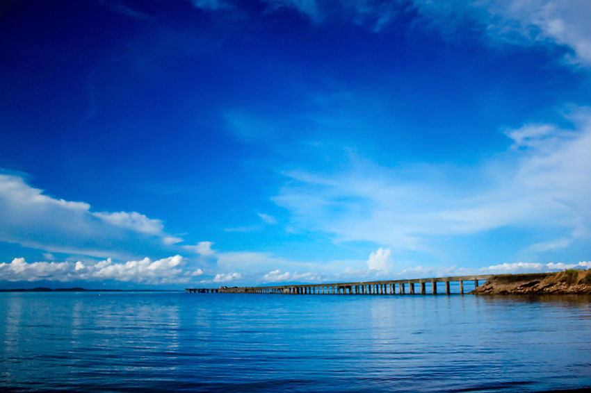 The bridge stretches to the sea. Bridge Over Water Architecture Beauty In Nature Blue Bridge Bridge - Man Made Structure Bridge View Built Structure Cloud - Sky Connection Day Landscape Sea Landscape Seascape Nature No People Outdoors Scenics - Nature Sea Sky Tranquil Scene Tranquility Transportation Water Waterfront
