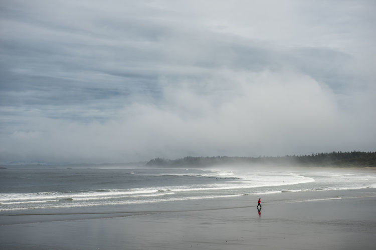 A person in a red coat walking on Long Beach in Tofino, British Columbia. Adult Beach Beauty In Nature Cloud - Sky Day Full Length Horizon Over Water Lifestyles Nature Ocean One Person Outdoors Pacific Northwest  Pacific Ocean People PNW Real People Scenics Sea Sky Standing Surf Tofino Water Wave Neighborhood Map