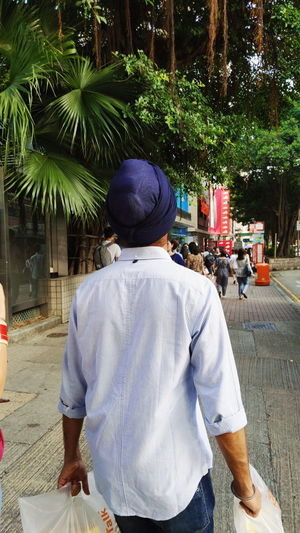 Rear view of man standing against trees in city