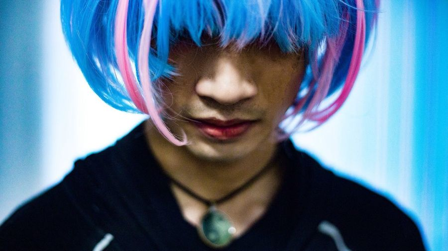 Close-up of young man wearing wig