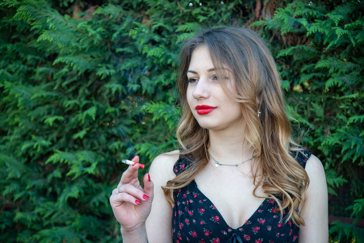 Beautiful woman holding cigarette against plants