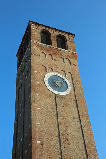 high clock bell tower in downtown of Chioggia Island near Venice in Italy Ancient Roman Number Architecture Bell Tower Bell Tower With Clock Belltower Building Exterior Built Structure Campanile Chioggia Clock Tower Clock Tower And History Clock Tower Of The City Clocktower No People Place Of Worship Religion Roman Clock Roman Numbers Roman Numeral Roman Numerals Tower