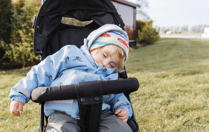 Girl Sleeping On Baby Stroller At Field