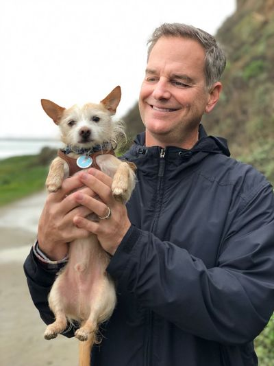 Smiling mature man holding dog while standing on road