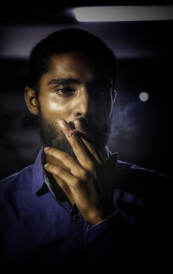 Young man looking away while smoking cigarette