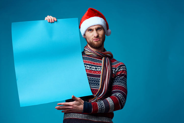 Portrait of young man holding hat against blue background