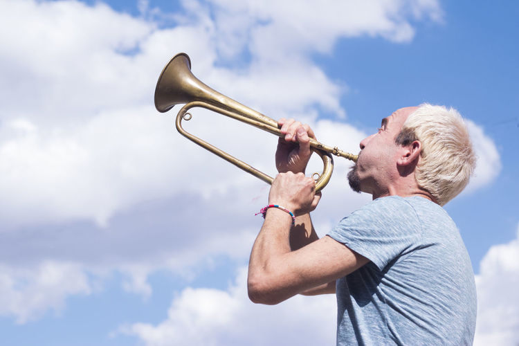 Adult Beard Brass Brass Instrument  Cloud - Sky Day Facial Hair Holding Leisure Activity Low Angle View Men Music Musical Instrument One Person Outdoors Side View Sky Trumpet Waist Up Wind Instrument