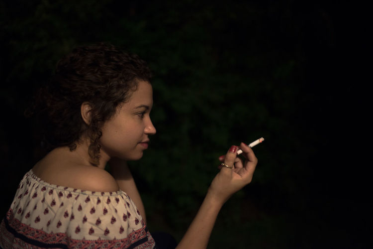 Close-up of young woman holding cigarette