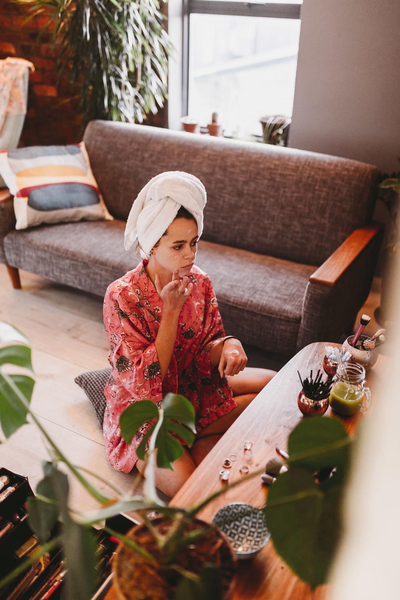 Woman applying facial mask while sitting at home