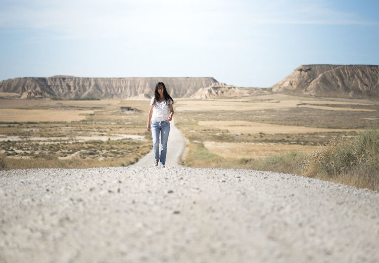 Full Length Of Mature Woman Walking On Road Against Sky During Sunny Day