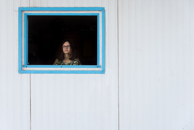 Portrait of woman looking through house window