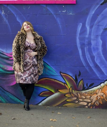 Full length of woman with graffiti on wall