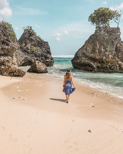 Tranquil Scene Long Hair Blue Dress Bingin Vertical Beach Walk Walking Tree On Rock Tree Rock - Object Ocean Sea Beach Water Land Sky Sand Real People Lifestyles Day Nature Beauty In Nature Leisure Activity Rear View One Person Sunlight Full Length Women Horizon Over Water Outdoors