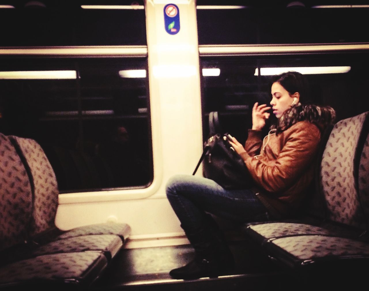 two people, sitting, wireless technology, mobile phone, real people, togetherness, transportation, young women, young adult, communication, public transportation, portable information device, women, indoors, leisure activity, technology, train - vehicle, full length, lifestyles, relaxation, young men, men, smiling, friendship, day, warm clothing, adult, people, adults only