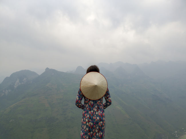 Young Vietnamese women facing and pose for camera with stunning view of the Nho Que river surrounded by mountains from the Ma Pi Leng pass in northern Vietnam Mountain Cloudy Green Color Meo Vac Vietnam Vietnamese Adult Ao Dai Beauty In Nature Cloud - Sky Environment Idyllic Landscape Leisure Activity Looking At View Mountain Mountain Range Nature Non-urban Scene One Person Outdoors People Pose Real People Rear View Scenics - Nature Sky Standing Sunrise Traditional Dress Tranquil Scene Valley Women