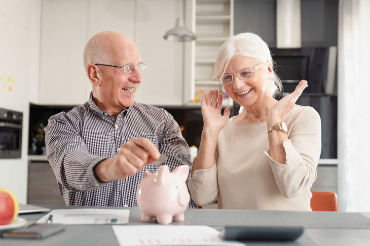 Senior couple inserting coin piggy bank over table