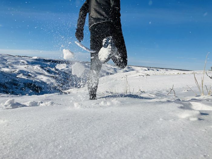 Low section of man running on snow