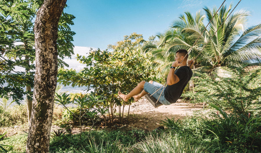 Side view of man sitting on swing against trees