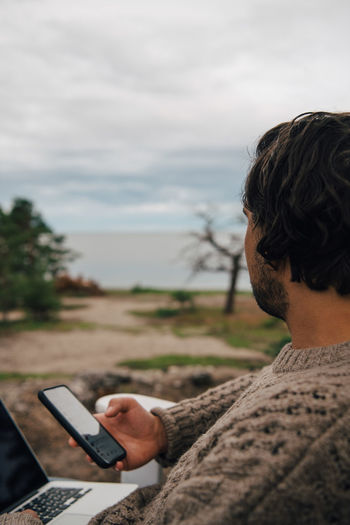 Portrait of man using mobile phone against sky
