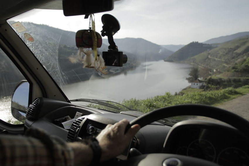 Looking through windscreen at mountain path and river Car Car Interior Dashboard Day Driving Human Body Part Human Hand Land Vehicle Landscape Men Mode Of Transport Mountain Nature One Person Outdoors People Real People Road Sky Steering Wheel Transportation Travel Vehicle Interior Windshield