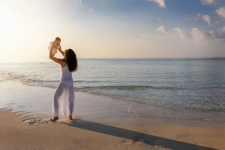 Mother playing with daughter while standing on shore at beach against sky during sunset