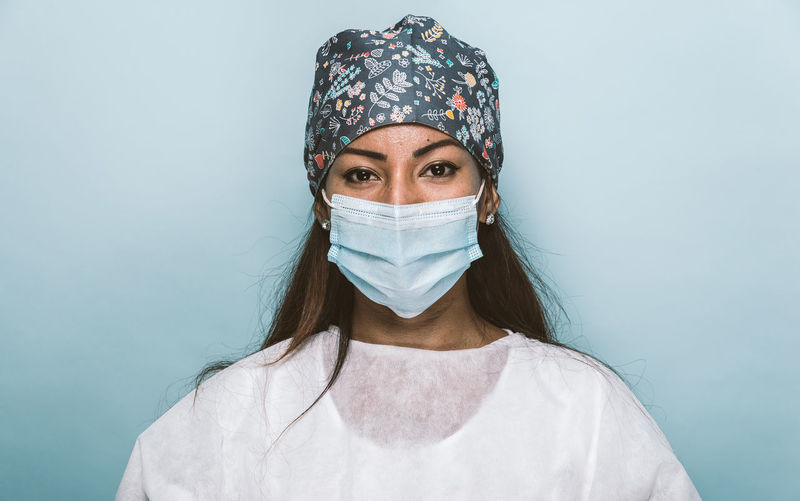 Portrait of doctor wearing mask standing against wall