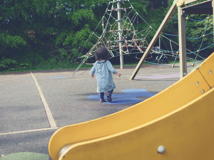 Rear view of baby girl walking at playground