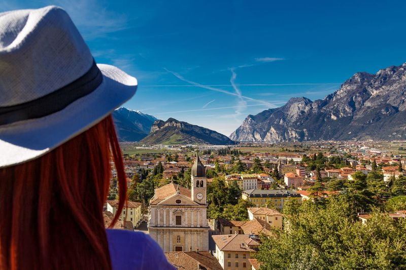 Rear view of woman looking at townscape against blue sky