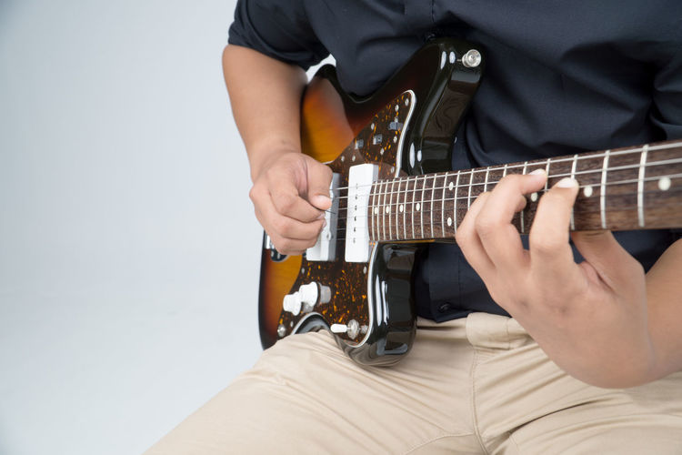 Arts Culture And Entertainment Close-up Day Electric Guitar Fretboard Guitar Holding Human Hand Indoors  Leisure Activity Lifestyles Men Midsection Music Musical Instrument Musical Instrument String Musician One Person Playing Plucking An Instrument Real People