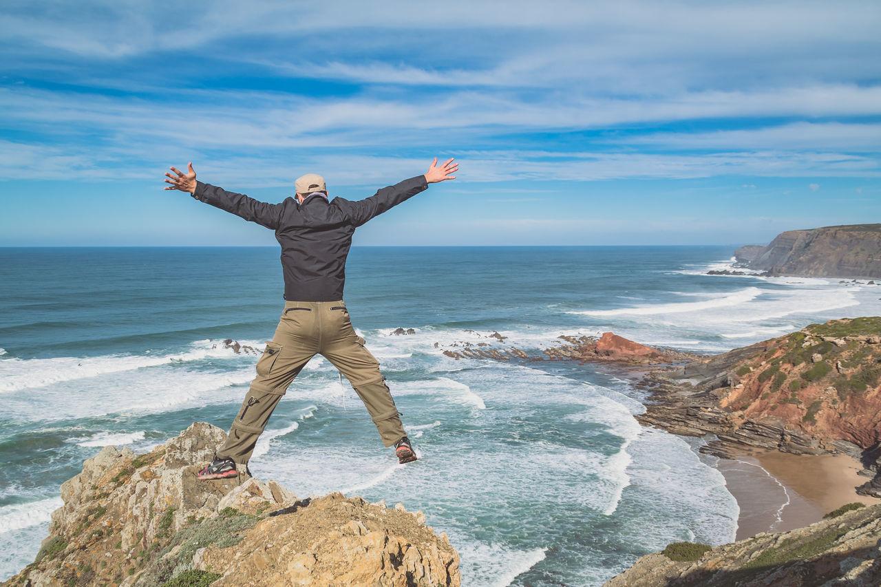 Man With Arms Raised On Beach Against Sky