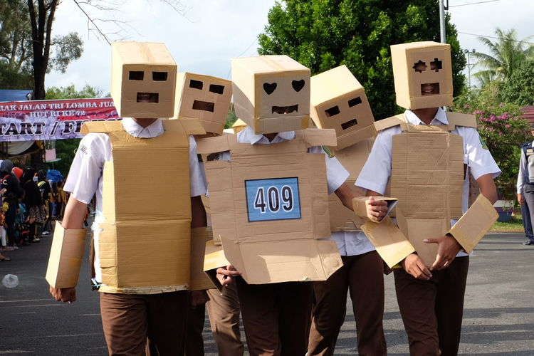Men wearing cardboard costumes on road