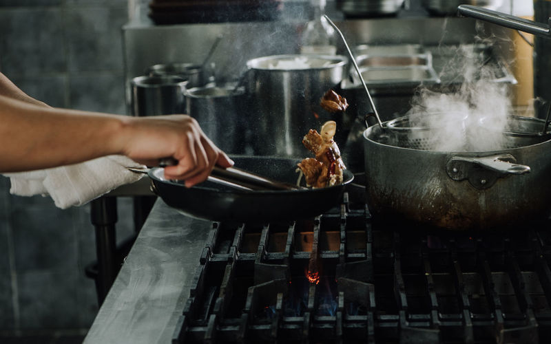 Cropped hands of person preparing food on stove