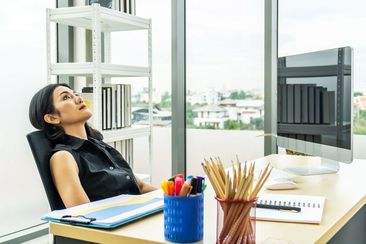 Woman looking at window while sitting on table